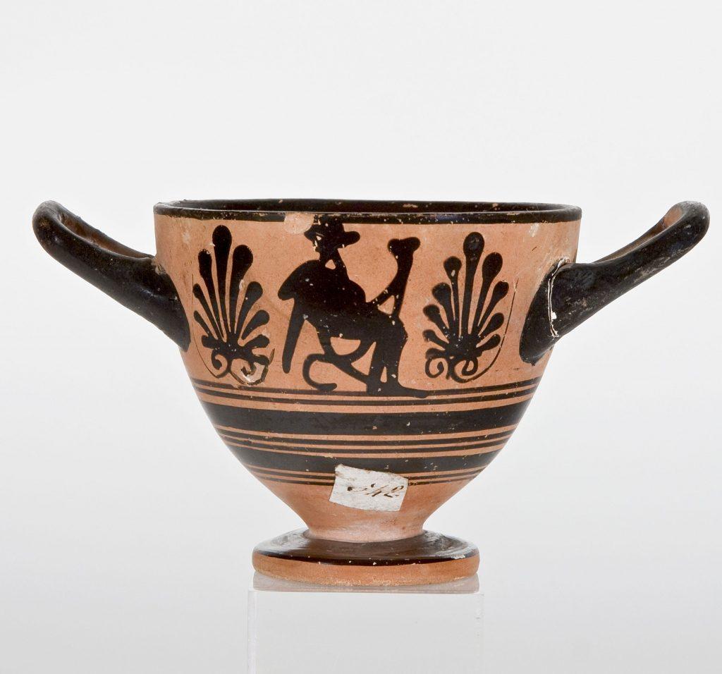 Coppa (skyphos) in ceramica attica a figure nere raffigurante Dioniso seduto con in mano un rhyton,